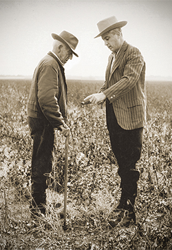 A picture of Edward Mauldin speaking with a farmer.