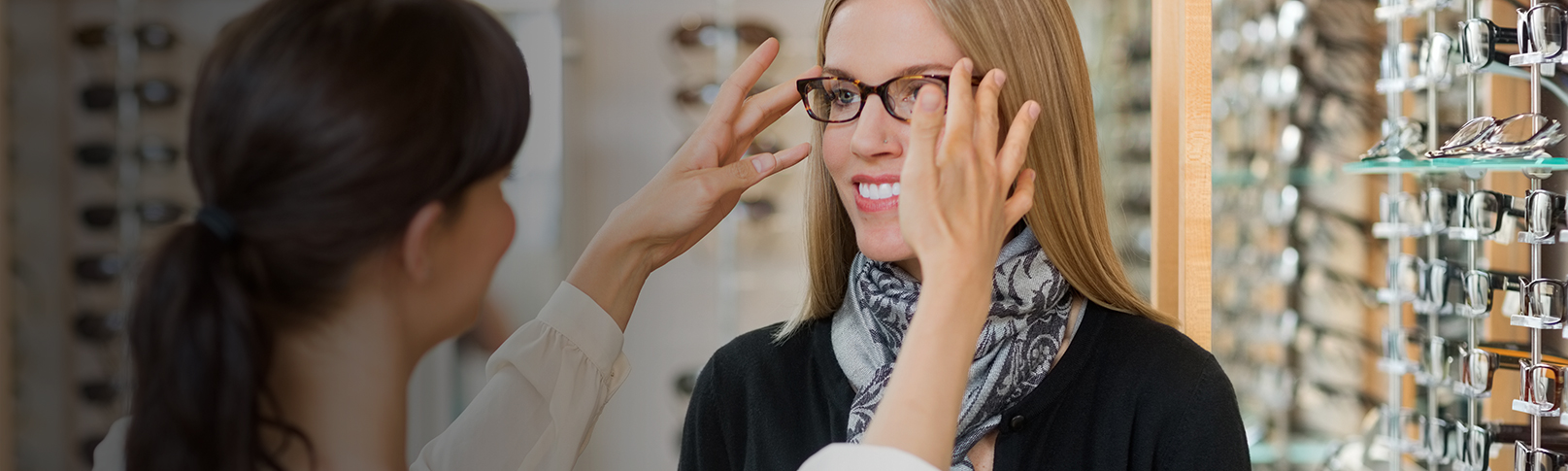 Optometrist helping a lady try on glasses