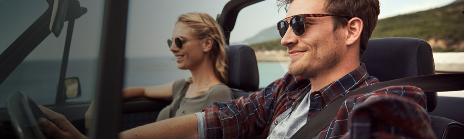 young couple driving in a convertible