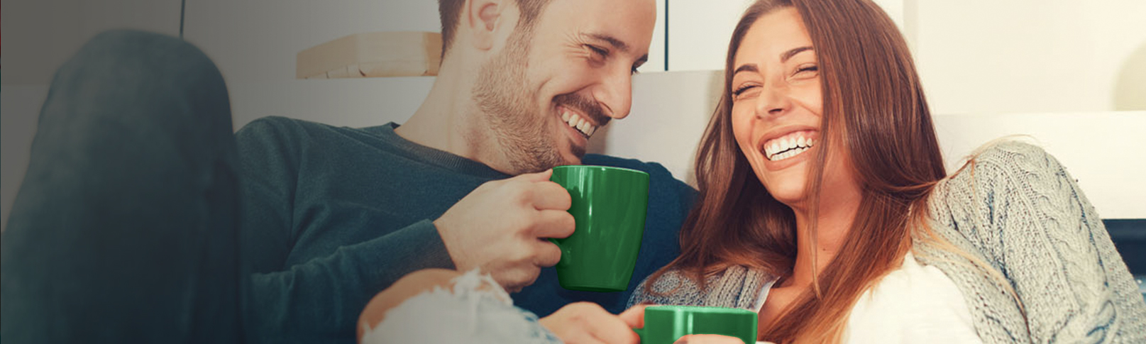 couple on couch laughing with coffee cups